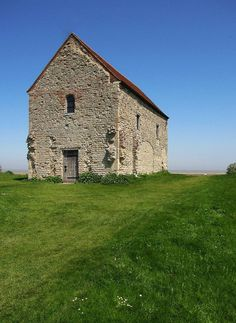"""The Chapel of St Peter on the Wall, Bradwell-on-Sea, Essex, England. The Chapel is a Grade I listed building and among the oldest largely intact Christian church buildings in England still in regular use, dating from the 7th century. The Chapel is assumed to be that of """"Ythanceaster"""" (Bede, Historia Ecclesiastica 3.22), originally constructed as an Anglo-Celtic Church for the East Saxons in AD 654 by St Cedd, astride the ruins of the abandoned Roman fort of Othona."""