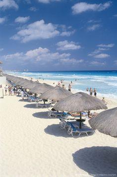 Straw huts on beach in Cancun, Mexico. Premiercruisesandvacations.com
