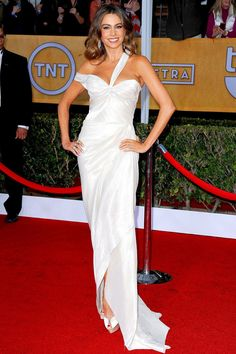 Sofia Vergara in Donna Karan Atelier, white liquid lamé gown with Charlotte Olympia peep-toes and a Jimmy Choo bag.