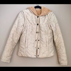 O'neill Lined Puffy Cream Jacket Softly lined jacket with snap buttons on front. Jacket is cream colored with tan leaf pattern. Two pockets with snap button closures. The hoodie is also lined for extra warmth. The sleeves unzip and detach so that jacket can be worn as a vest. O'Neill Jackets & Coats