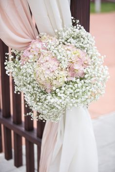 Light pink and ivory draping with simple floral display tying them together off to the side.