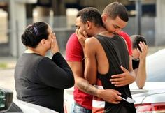 Friends and family members embrace outside the Orlando Police Headquarters during the investigation of a shooting at the Pulse night club after a mass shooting on June 12, 2016.