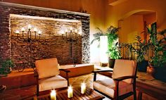 Patio furniture, candles on the table, stone wall