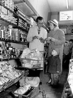 1950sYoung shop assistant advising mother and child in a supermarket.