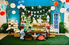 A empresa Joana e Maria (www.facebook.com/joanaemariafestas) usou na decoração da festa com tema Smurfs na floresta um painel feito com muro inglês (estrutura revestida com folhas artificiais), que levou aplicações dos personagens impressos saindo da folhagem