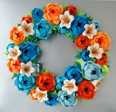This rose wreath is entirely made out of paper. The flowers are very close to life size. This arrangement includes 3 different shades of blue, 2 shades of