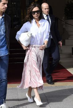 She means business: Maintaining her trademark workwear vibe, Victoria paired the skirt with a simple white collared shirt