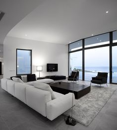 Apartment. An Inspiring Contemporary Building in Colunta for Luxurious Lifestyle: Remarkable Home Design With Spacious Living Room Comfortable White Sofa Intriguing Wooden Coffee Table Elegant Table Lamp Luxurious Fur Rug Stunning Black Arm Chair Extensiv