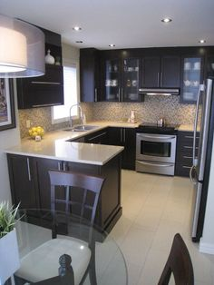 Espresso color cabinets, square framing, new hardware, light colored counter tops, neutral mosaic tile backsplash
