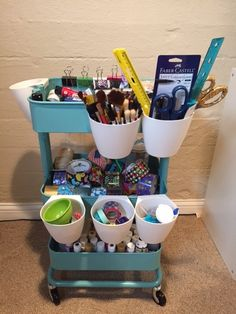 """My crafty daughter needed a place for paint, """"duck"""" tape, scissors, pens, markers...the list goes on. The turquoise, metal rolling cart was $29.99 at IKEA (RASKOG - office section), and the white hanging cups were 99 cents ea. (BYGEL - kitchen section). Now everything is all in one place and can be moved around, based on what location inspires my little artist!"""