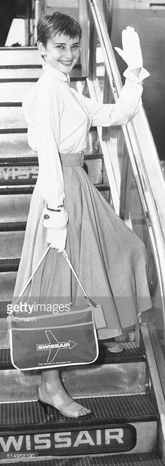 Pretty award winning stage and screen actress Audrey Hepburn waves goodbye to New York as she boards a Swissair plane at Idlewild Airport, for a flight to Switzerland. Miss Hepburn said she would take a vacation and then go to England to make another film.