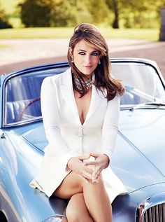 Elizabeth Hurley. Elegant in a white blazer & chunky necklace atop a vintage car