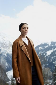 Hermès - Vestiaire d'Hiver 2013. Trench coat in vicuna full-grain lambskin, sleeveless V-neck pullover in tobacco camel hair, bib-front shirt in white cotton poplin, trousers in overdyed ink cashmere flannel with stitch detailing. #hermes #fashion