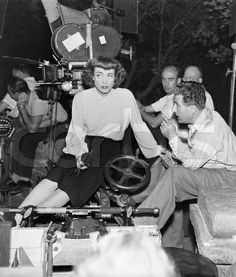 "Hollywood, Los Angeles, California, USA --- 7/17/46-Hollywood, California: Academy Award-winning star Joan Crawford listens to instructions from director Curtis Bernhardt during a between-scenes confab on the set of ""possessed."" The actress, who always knits during spare moments on the set, holds her knitting. --- Image by ? Bettmann/CORBIS"