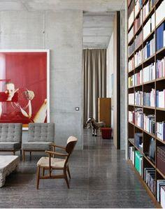 FULL HEIGHT TIMBER BOOKSHELF. POLISHED CONCRETE FLOOR. CEMENT RENDER WALLS. High ceilings. Red artwork.: