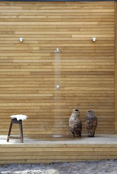 Maybe plank the wall behind the outdoor shower fixures?