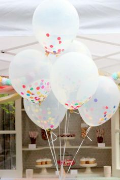 Cómo hacer originales globos llenos de confetti: Coges el confetti en pequeños puñaditos y los metes por la boquilla del globo. Ayúdate de la parte trasera de un lápiz o bolígrafo para ir metiendo hacia dentro el confetti con cuidado de no romper el globo. Cuando tengas unos cuantos metidos ya puedes inflar el globo normalmente. Tus globos se quedarán como los de la fotografía.