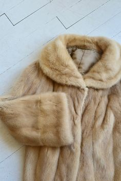 "Super soft and plushy late 1950s, early 1960s blonde mink coat with rounded collar (can also be worn fipped up), sleeves that widen toward the cuff, pockets and champagne floral satin lining. --- M E A S U R E M E N T S --- fits like: medium shoulder: approx. 15 bust: up to 40 sleeve: approx. 22 length: 24 brand/maker: n/a condition: excellent ★ layaway is available for this item ➸ More vintage coats <a href=""http://www.etsy.com/shop/DearGolden?section_id=5800175"" rel=""nofollow"" target=""_blank"">www.etsy.com/...</a> ..."