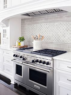 Range hood with pretty backsplash design. I like this soft gray in the white cabinet surround
