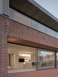 Rear view of the house at Broad Street in Suffolk by Nash Baker Architects, showing the local handmade red bricks used on the ground floor, and views of the sitting room and kitchen.