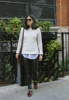 Wear a Gap cable knit sweater over a collared shirt for a classic fall look. The Style Line blog shows how to pair a white Gap sweater with vegan leather pants and burgundy accessories.