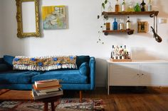 Anthropologie's Collaged Majida Throw Blanket sits atop the sofa. A small bar sits atop an IKEA cabinet.
