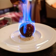 Henri Charpentier's <<Dome>> - chocolate dome encapsulating strawberry slices, almond biscuits, flambé with strawberry liquor.