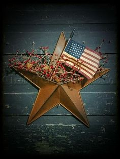"""A 16"""" rusty star pocket filled with pip berries and rusty stars with two keyholes in the arms of the star for hanging. Add an Americana flag for a patriotic touch. ***Americana Pip Berries are mixes w"""