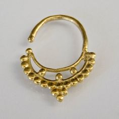 Beautiful Brass Septum For Pierced Nose - Body Jewelry - Septum Jewelry - Indian Nose Ring - Ethnic Septum - Septum Piercing - Nose Jewelry  This gorgeous traditional septum is made of brass and decorated with small brass balls.   For pierced nose. Can be worn on the ear as well.  Nickel Free.  The bar is 1mm. 18 Gauge Total diameter: 10mm. $14.5