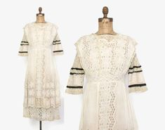 Vintage Edwardian ivory cotton lace dress with black silk trim in a wearable modern size and lovely overall condition. Soft semi sheer cotton voile with layered pintucked skirt and heavily embroidered floral pattern and handmade eyelet detail. Trimmed with contrasting lace and black silk strips. Classic layered long skirt. Closes down the back with hidden buttons in loops and snaps at the fitted waist. Fully lined in sheer net; you will likely want to pair with a slip. Label: Bellas Hess…