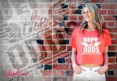 """Fly Elephant's """"Defy The Odds"""" campaign design is on a orange tee for the ladies. Don't forget proceeds from Fly Elephant shirt sales go to American Cancer Society! http://modera.co/home/#contests"""