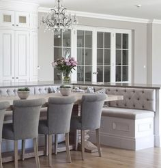 Upholstered bench seating is housed in the large island of this Hampton kitchen, perfect for entertaining! | #hayburnco • • • •…