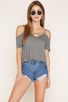 A knit open-shoulder top with crisscross straps at its V-neckline, cami straps, short sleeves, and a V-cut back.