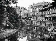 De Oude Gracht te Utrecht met kaden en de werfkelders met bedrijfjes. Boven aan de straat staan grote stagige panden (huizen). Utrecht, jaartal onbekend.