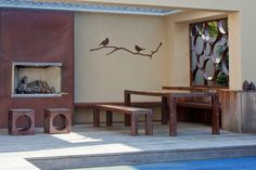 Rivet outdoor table and benches, custom fireplace facade, Wingter Bird wall art, hand-rolled Bubble Candle screening