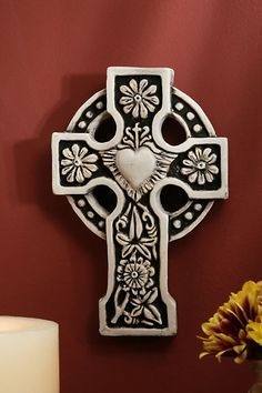 This lovely cross design was found near Ballyshannon in Co. Donegal, Ireland. At the center is the sacred heart of Jesus with rays of light surrounding it. The outer ring is thought to represent heave