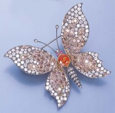 A DIAMOND AND COLOURED DIAMOND BUTTERFLY BROOCH  With pavé-set diamond and coloured diamond wings to the oval-cut orange sapphire and pink sapphire eyes