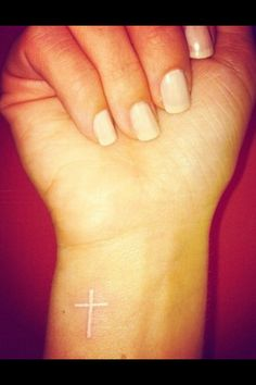 white ink cross tattoo on inner wrist.
