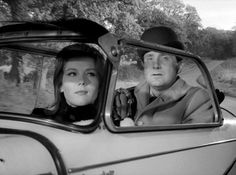 Emma drives while Steed is squeezed into the back of the tiny Messerschmidt car as they drive away