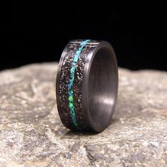 Meteorite Shavings with Blue Green Lab Opal Inlay Carbon Fiber Wedding Band or Ring by HolzRingShop on Etsy https://www.etsy.com/listing/241178275/meteorite-shavings-with-blue-green-lab