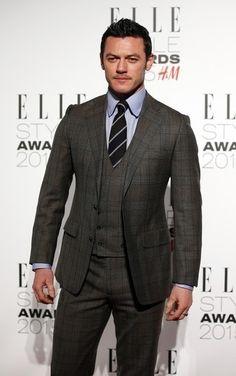 Luke Evans wearing Charcoal Plaid Three Piece Suit, Grey Dress Shirt, Black Vertical Striped Tie