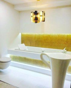 The LA LOLLO #pendantlamp looks gorgeous in its gold/fumè medium version, featured in this #tiled #bathroom by our friend Bartico Bartycka, #Precious metallized and #brushed cylinders envelop the #LED light, enchanting the #warm and #elegant space. Discover more www.slamp.com