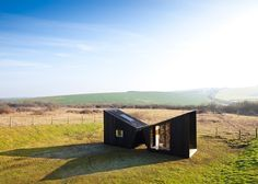 Observatory by Feilden Clegg Bradley house artist's studios. These two charred-timber cabins house a temporary artist's studio that will travel across the UK, offering passers-by a glimpse into the working processes of the occupants.