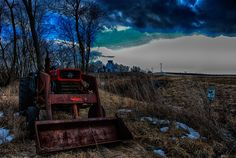 A forgotten tractor along a cold winter highway by Kim Ladd - A dark brooding sky overshadows a stark landscape of fallow farm fields and a lone tractor Click on the image to enlarge.
