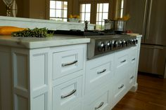 Pilaster column corners and inset doors and drawers create a smart profile that only adds to the simple design of this cook top, integrated into a kitchen island with bar seating.  #white #kitchen #remodel #home #counter #top #range #valance #toe #stone #island #bar #flat #shaker #drawers