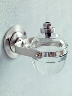 A stylish alternative to traditional pumps, our stylish soap dispenser has been carefully crafted from weighty glass with a simple silver brass frame. This vintage inspired wall mounted dispenser will look beautiful beside the kitchen sink or in the bathroom - simply tip the glass globe to dispense the soap.