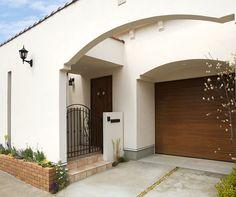 インナーガレージ付の中庭型住宅。プライバシーを守るための塀と外壁が一体になったデザインです。 南欧風住宅・プロヴァンス アーチ 砂岩  ビルトインガレージ 