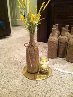 Centerpieces I made for my outdoor wedding.  Spray paint cake board with gold foil. Wrap mason jar with lace. Add rocks and candle. Wine bottle wrapped in twine. Flowers of your choice and ta-da!
