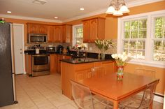 New Eat-in Kitchen (11' x 13') with ceramic tile floor, custom oak cabinets, pantry cabinet with pullout shelves, granite counters with travertine back splashes, stainless steel dishwasher, stove, microwave, refrigerator with French doors and bottom freezer, crown molding and recessed lighting