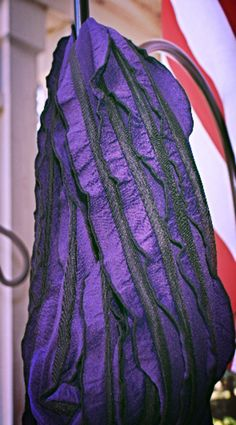 Take a walk on the wild side with this deep purple ruffled scarf has a black stripe and multicolored beaded tassels including purples and animal prints.